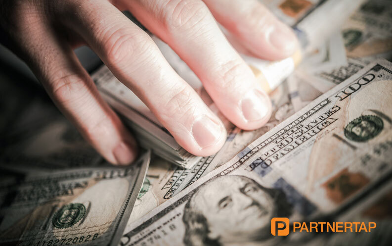 A Hand Holding Money that has been made using an automated account mapping solution